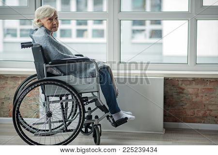Upset Mature Woman Looking At Camera With Sad Look. She Is Sitting In Wheelchair In Room Wrapped In