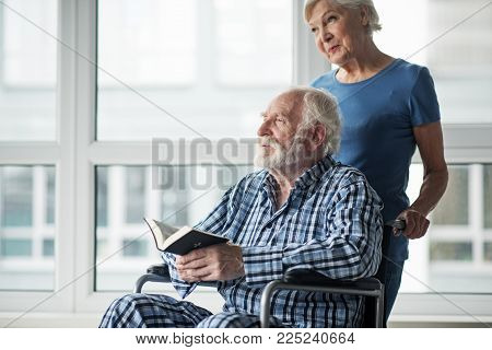 Tranquil Senior Husband Sitting In Wheelchair And Holding The Bible. His Calm Wife Standing Near Him