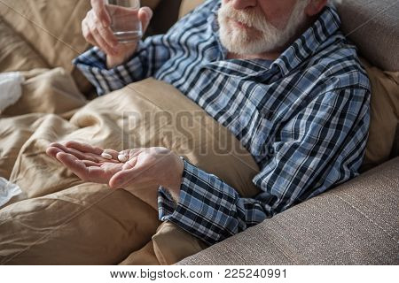 Senior Male Is Ill And Taking Medicine At Home. He Is Lying In Bed While Holding Pills And Glass Of