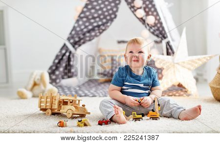 baby boy with toy cars in the children's playroom