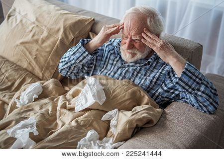 How It Hurts. Exhausted Old Male Having Headache In Bedroom. He Is Sitting In Bed And Holding His He