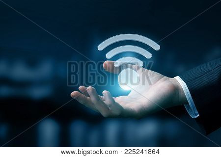 Hand of a businessman shows the WIFI symbol on a blue background.