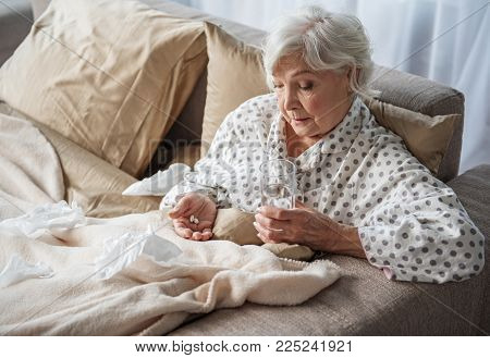 Upset Old Woman Sitting In Bed With Sad Look. She Is Looking At Medication In Hands And Holding Glas