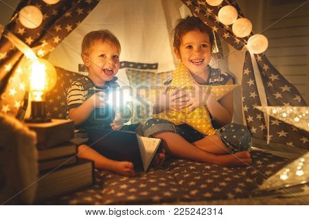 children boy and girl reading book with flashlight in  tent at night
