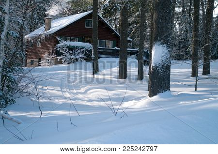 Smoke curling from a log cabin in the winter