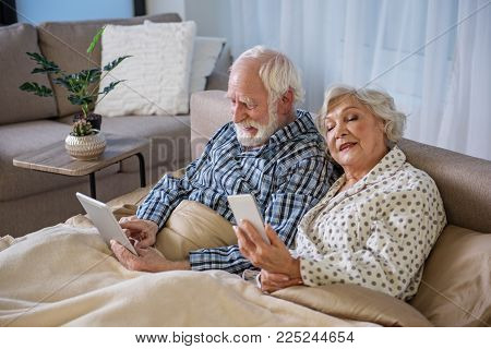 Tranquil Elderly Couple Surfing The Internet In Bedroom. They Are Looking At Devices And Reading New