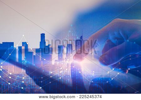 Close up of hand using tablet with abstract digital business hologram. City background. Technology, innovation and touchscreen concept. Double exposure