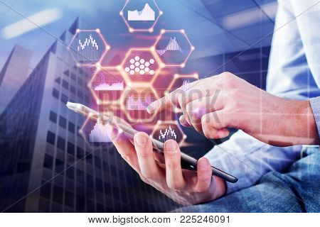 Close up of hand using tablet with abstract digital business hologram. City background. Technology, innovation and communication concept. Double exposure