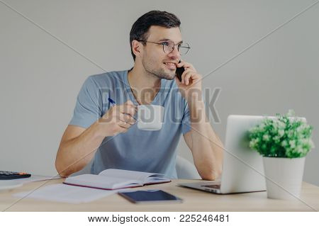 Handsome brunet male in round spectacles and casual t shirt, drinks hot beverage, has telephone conversation while works at office desk with laptop computer and documents. Communication concept