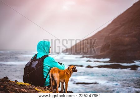 Man with a dog in front of rural coastline landscape with mountains and waves and sun rays comming through the clouds. Santo Antao Island, Cape Verde.