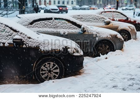 Cars parked in city covered with snow. Heavy snowstrom paralysed town. Vehicles in snow on parking lot. Winter scene and bad weather conditions