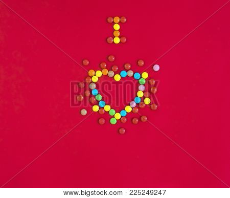 on a red background written with sweets I love in the form of a heart with multi-colored round candies