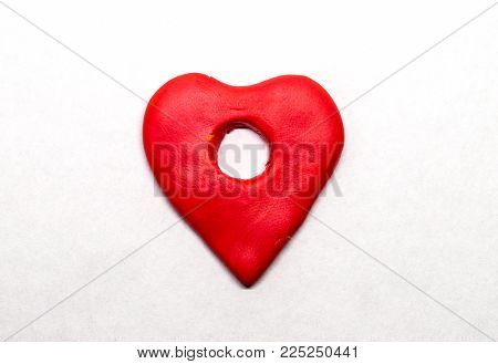 Red heart pointer isolated. Modelling clay navigation sign on white background. Heart pointer in naive nursery style. Children hobby modeling. Handmade heart. Road map navigation. Love point symbol