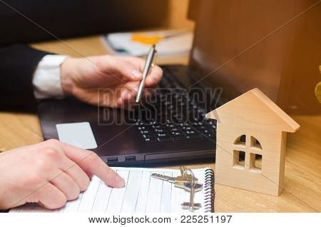 real estate buying an apartment. Real estate agent putting signing contract, sitting at the computer. moving home or renting property. focus on the house