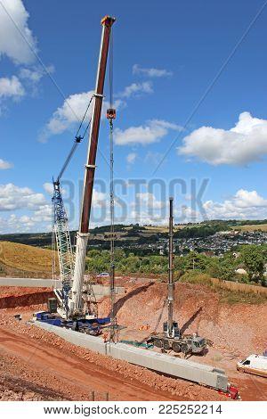 Crane Lifting A Concrete Beam For A New Bridge