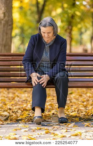 Senior woman sitting on bench in autumn park and having knee pain. Arthritis pain concept. Focus on her face.