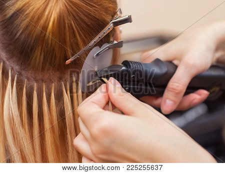 The Hairdresser Does Hair Extensions To A Young Girl, A Blonde In A Beauty Salon. Professional Hair