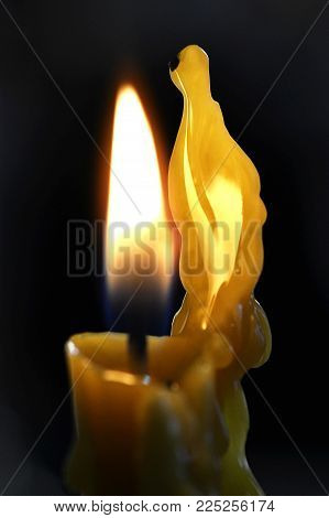 Lighted Candle Wick With Melted Wax Side On A Black Background