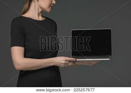 cropped shot of attractive woman holding laptop with blank screen isolated on grey