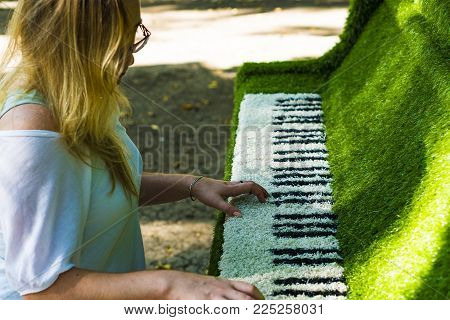 The girl at the piano. The tool is covered with a decorative cloth. Simulation of the game. A woman in glasses plays the decorative piano.