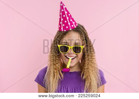 Happy teenage party girl 12-13 years old. Girl with pink background, in festive hats, blowing in the pipes