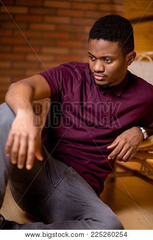 African man sitting on the floor and looking at camera