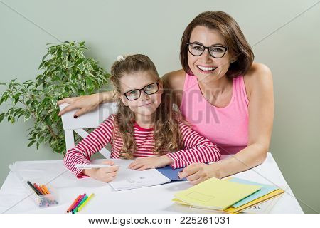 Loving mother helping her daughter elementary school pupil write in her notebook, at home at the table. Back to school concept.
