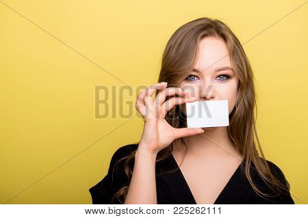 Cheerful young woman holding bank card isolated on a yellow background