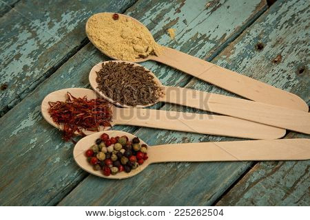 saffron, pepper, cumin and mustard in a wooden spoons