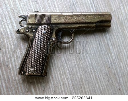 Pistol souvenir of yellow color looks like a real on a gray background of a parquet of a table of a laminate