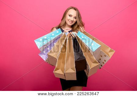cheerful young girl holding shopping bags and looking at camera isolated over pink background
