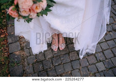 legs and shoes bride in a dress with a bouquet on a stone road outside