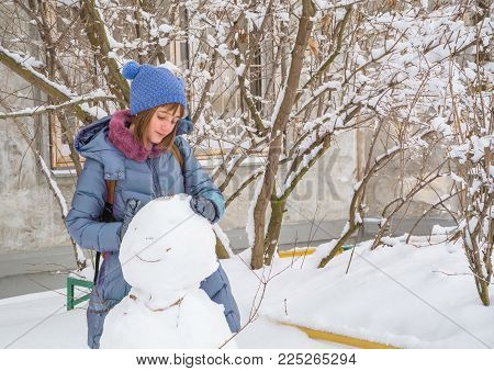teenage girl sculpts snowman out of snow