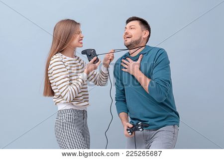 Angry woman strangling her husband with cord from video game controller on color background