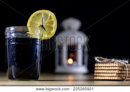 Cooling Drink In A Glass On A Wooden Table. In The Background A Lantern With A Glowing Candle.