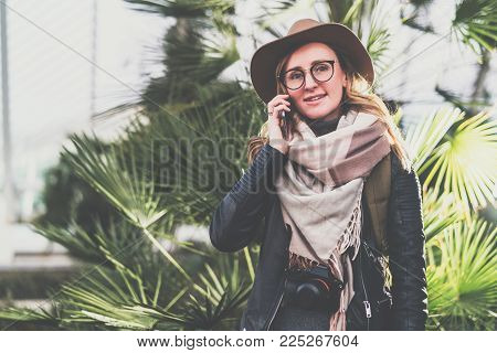 Young smiling woman tourist with backpack in hat and eyeglasses stands in city park and talks on cell phone. Girl traveler using digital gadget, enjoying vacation. Tourism, travel, voyage, trip.