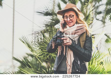 Young smiling woman tourist photographer in hat stands outdoor, talks on cell phone, looks on screen of camera. Girl traveler using digital gadget, enjoying vacation. Tourism, travel, voyage, trip.