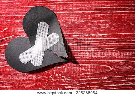 Torn paper heart with medical plasters on wooden background. Relationship problems