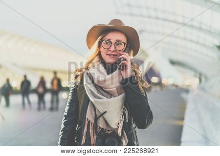 Young smiling woman tourist with backpack in hat and eyeglasses stands on city street and talks on cell phone. Girl traveler using digital gadget, enjoying vacation. Tourism, travel, voyage, trip.
