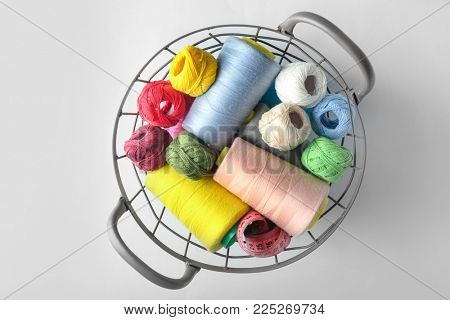 Metal basket with color sewing threads and crocheting clews on light background, top view