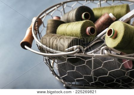 Metal basket with color sewing threads on grey background