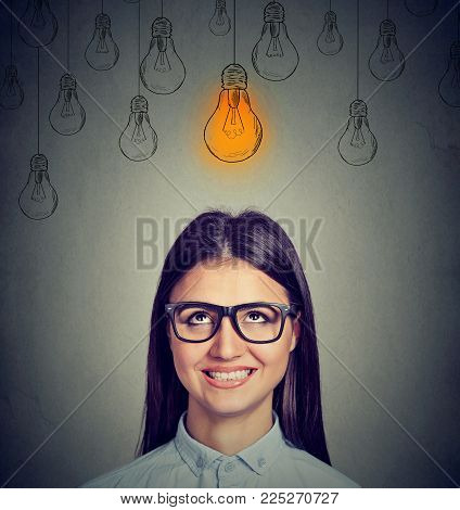 Excited Happy Woman In Glasses Looking Up At Bright Light Bulb Above Head Has An Idea Isolated On Gr