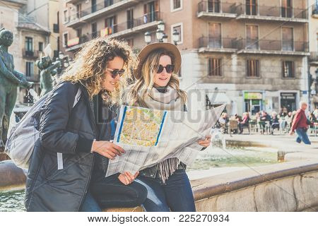 Two young smiling tourist women are sitting on city street near fountain and are looking for way on map. Girls sit bent over the map of destination. Vacation, travel, tourism, sightseeing.