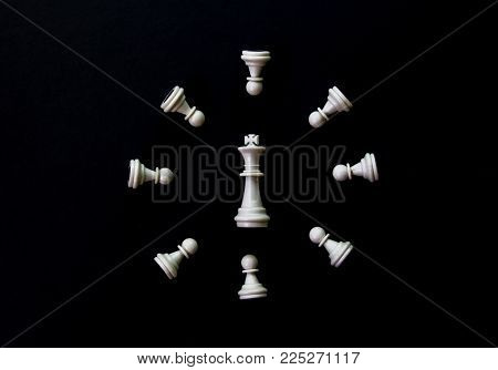 White chess clock on black background flat lay photo. White chess figures abstract ornament. Chess on table flat lay. Chess clock top view photo. Checkmate game banner template. Intellectual sport