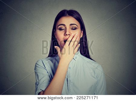 Sleepy woman with wide open mouth yawning eyes closed covering mouth with hand isolated on gray background. Human face expression body language