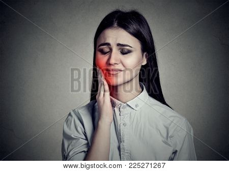 Woman with sensitive toothache crown problem suffering from pain touching outside mouth with hand isolated on gray background. Negative human emotion feeling