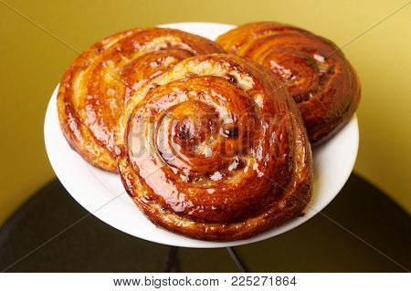 Freshly Baked French Pastries. Delicious homemade baked pastry swirl on yellow background, close-up