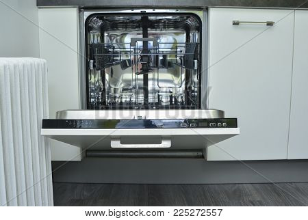 Modern white dishwasher with an open door on the kitchen