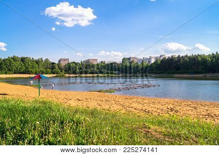 Natural forest lake with artifical sandy beach, been adjusted for free public leisure activities. Moscow residential suburb, Zarya district, Balashikha.