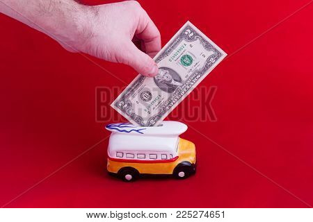 money box, in the form of a ceramic bus with a denomination of two dollars, on a red background. The concept of saving money. Accumulation for rest. Concept of savings or charity.